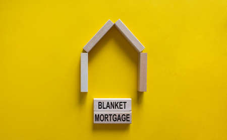 Model of a wooden house. Words 'blanket mortgage' on wooden blocks. Copy space. Business concept. Beautiful yelllow background.