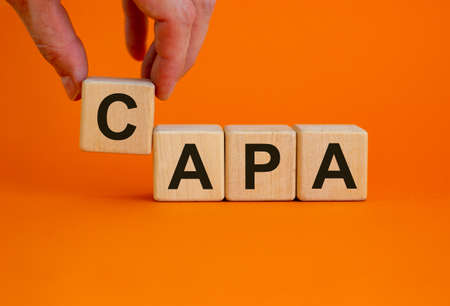 Concept words 'CAPA, corrective and preventive actions' on wooden cubes on a beautiful orange background. Male hand. Business concept. Copy space.