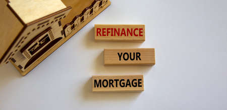Wooden block form the words 'refinance your mortgage' near miniature house. Beautiful white background, copy space.