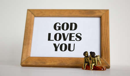 Wooden picture frame with inscription from Bible on beautiful white fon. Two bronze angeles on the table.
