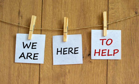 Wooden clothespins with white sheets of paper with words 'we are here to help'. Beautiful wooden background. Business concept, copy space. Banco de Imagens