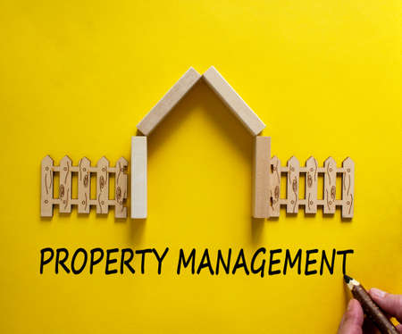 Hand writing 'property management' on beautiful yellow background. Model of a wooden house. Male hand, wooden fence. Copy space. Business concept.