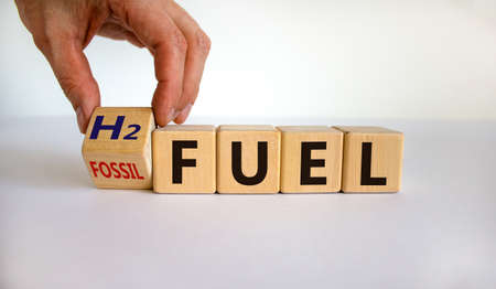 Hand turns a cube and changes the expression 'H2 fuel' to 'fossil fuel'. Beautiful white background. Copy space.