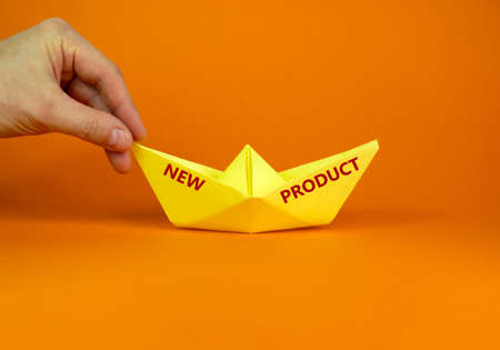 Image of businessman pushing paper made origami boat forward in a conceptual image. text 'new product'. Over orange background with copy space. Business concept.