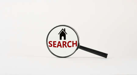 Magnifying glass with text 'search' and house icon on beautiful white background. Business concept, copy space.