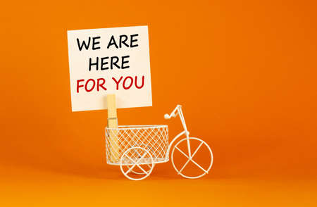 Wooden clothespin with white sheet of paper. Text 'we are here for you'. Miniature bicycle model. Beautiful orange background. Business concept, copy space. Banco de Imagens