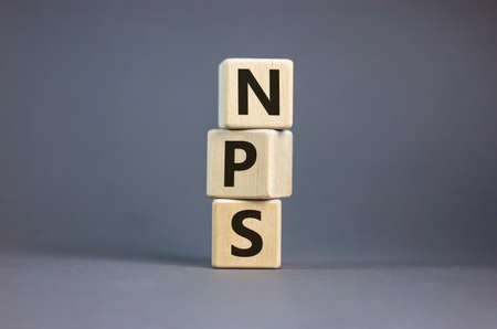 Wood cubes with acronym 'NPS' - 'net promoter score' on a beautiful gray background. Business concept, copy space.