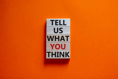 Wooden blocks with text 'tell us what you think'. Beautiful orange background, copy space. Business concept.
