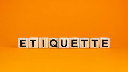 Concept word 'etiquette' on cubes on a beautiful orange background. Business concept. Copy space.