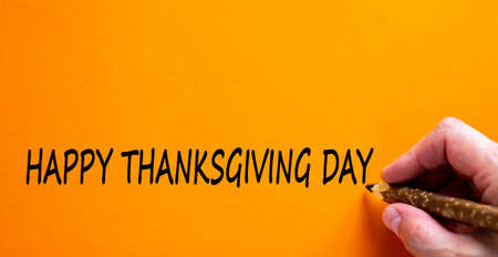 Hand writing 'Happy Thanksgiving Day', isolated on beautiful orange background. Celebration concept, copy space. Banco de Imagens