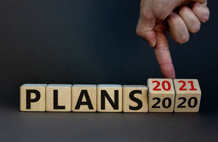 Business concept of planning 2021. Male hand flips wooden cubes and changes the inscription 'Plans 2020' to 'Plans 2021'. Beautiful gray background, copy space.