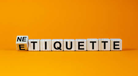 Etiquette or netiquette. Turned cube and changed the word 'etiquette' to 'netiquette'. Beautiful orange background. Business concept. Copy space.