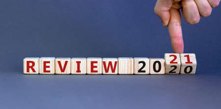 Business concept of starting 2021. Yand flips wooden cubes and changes the words 'Review 2020' to 'Review 2021'. Beautiful gray background, copy space. Stock Photo