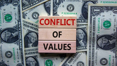 Conflict of values. Wooden blocks with words 'conflict of values'. Beautiful background from dollar bills. Copy space. Business and conflict of values concept.