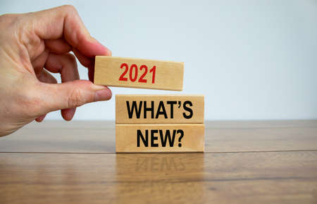 Wooden blocks with words '2021 whats new'. Beautiful wooden table, white background, male hand. Copy space. Business concept.