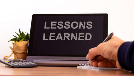 Education concept. Tablet with text 'lessons learned'. Online education during COVID-19 quarantine. Male hand with pen, calculator, copy space.
