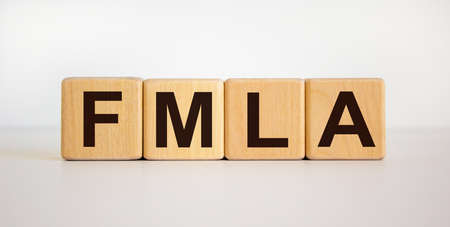 Concept words 'FMLA, family medical leave act' on wooden cubes on a beautiful white background. Copy space. Medical concept.