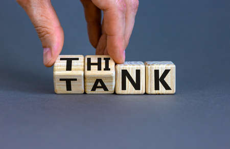 Think Tank concept. Blocks form the expression 'think tank'. Male hand. Beautiful gray background. Business concept. Copy space.