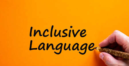 Hand writing 'inclusive language', isolated on orange background. Business and better inclusive concept. Copy space. Stock fotó