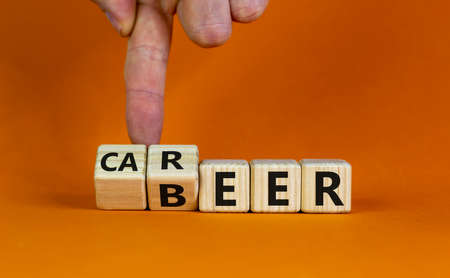 Career or beer. Male hand flips wooden cubes and changes the word 'beer' to 'career' or vice versa. Beautiful orange background, copy space. Business and career or beer concept. Stop drinking alcohol concept.