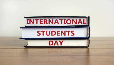 Books with text 'International Students Day' on beautiful wooden table, white background. Business and educational concept. Copy space. 版權商用圖片