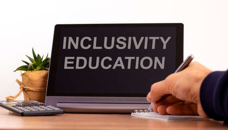 Education and inclusivity concept. Tablet with text 'inclusivity education'. Online education during COVID-19 quarantine. Male hand with pen, calculator, copy space.