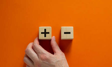 Plus or minus. Businessman holds a cubes with plus icon. Wooden cube with minus icon. Beautiful orange background. Copy space. Business and plus and minus concept. Stok Fotoğraf