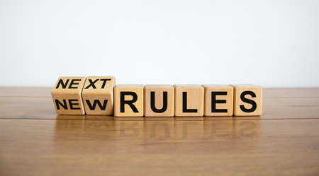 Time to next rules. Turned cubes and changed words 'new rules' to 'next rules' on a beautiful wooden table, white background. Business and covid-19 pandemic concept.