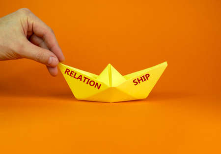 Image of businessman pushing paper made origami boat forward in a conceptual image. Words 'relation ship'. Over orange background with copy space. Business and relationship concept.