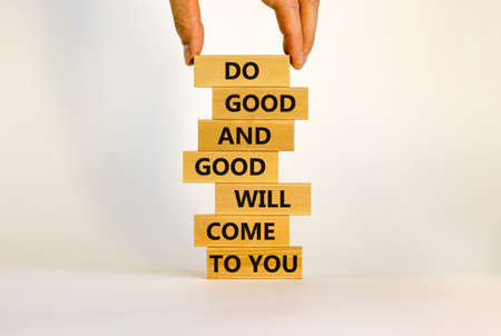 Concept of karma motivational words. Wooden blocks on the stack of wooden blocks. Words 'do good and good will come to you'. Beautiful white background, copy space. Imagens