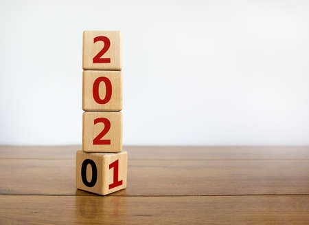2021 new year symbol. Turned cubes and changed the year '2020' to '2021'. Beautiful wooden table, white background. Copy space. Business and 2021 new year concept. Standard-Bild