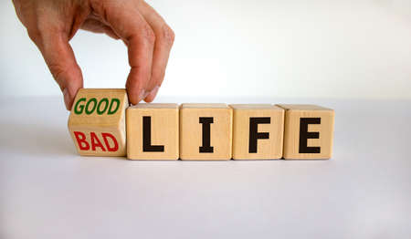 From bad to good life. Hand is turning a cube and changes the words 'bad life' to 'good life'. Beautiful white background. Business and good life concept, copy space.