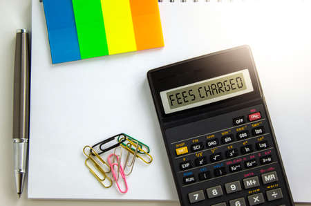 Fees charged symbol. Calculator with words 'fees charged', white note, colored paper, paper clips, pen. Business and fees charged concept. Beautiful white background, copy space.