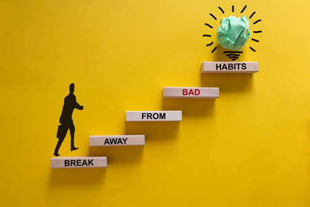 Business concept growth success process. Wood blocks stacking as step stair on yellow background, copy space. Businessman icon. Words 'break away from bad habits'. Copy space. Standard-Bild