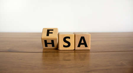 FSA or HSA symbol. Turned a cube and changed the word 'FSA - Flexible Spending Account' to 'HSA - Health Savings Account'. Beautiful wooden table. White background. Business and FSA or HSA concept.