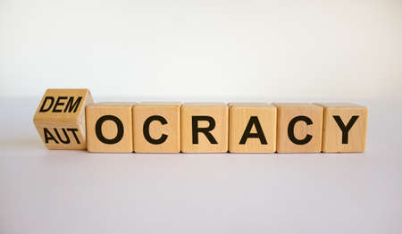 Democracy or autocracy symbol. Turned a cube and changed the word 'autocracy' to 'democracy'. Beautiful white background, copy space. Business and democracy or autocracy concept.