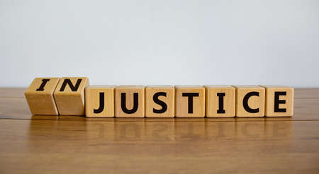 Justice instead of injustice. Turned cubes and changed the word 'injustice' to 'justice'. Beautiful wooden table, white background, copy space. Business and justice or injustice concept.