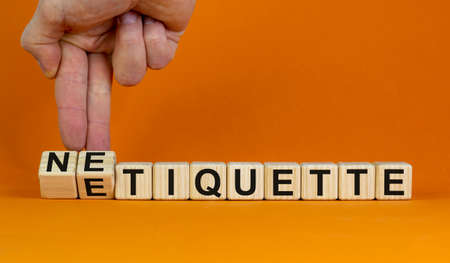 Etiquette or netiquette. Male hand turns cubes and changes the word 'etiquette' to 'netiquette'. Beautiful orange background. Business and netiquette concept. Copy space.