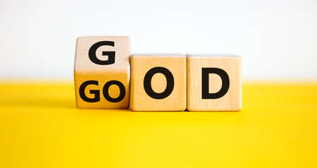 God is good symbol. Turned a cube with words 'God is good'. Beautiful yellow table. White background. Religion and God is good concept.