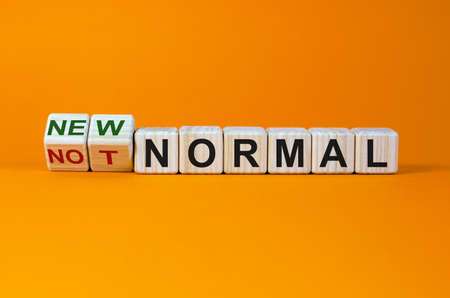 Covid-19 new normal symbol. Turned cubes and changed the words 'not normal' to 'new normal'. Covid-19 postpandemic new normal concept. Beautiful orange background, copy space.