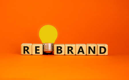 Rebrand symbol. Wooden cubes with word 'rebrand'. Yellow light bulb. Beautiful orange background. Business and rebrand concept. Copy space.