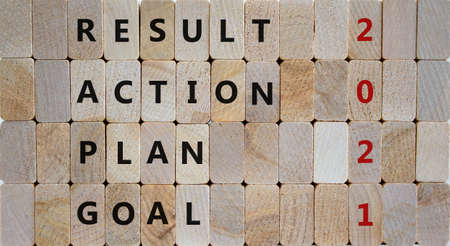Business concept of planning 2021. Wooden blocks with the words 'goal, plan, action, result'. 2021 number. Beautiful wooden background, copy space. 2021 new year symbol.