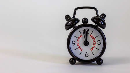 Time to review concept. Beautiful black alarm clock with words 'time to review'. White table. Beautiful white background. Copy space. Business and time to review concept.