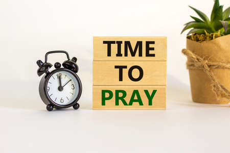 Time to pray symbol. Wooden blocks with words 'time to pray'. White table. Black alarm clock and house plant. Beautiful white background. Copy space. Religion and time to pray concept.