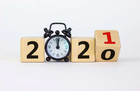 Business concept of 2021 new year. Turned a wooden cube and changed number 2020 to 2021. Black alarm clock. Beautiful white background, copy space. 2021 new year concept.
