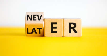 From later to never symbol. Turned a cube and changes the word 'later' to 'never'. Beautiful yellow table. White background. Busines and later to never concept. Archivio Fotografico