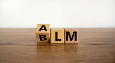 BLM vs ALM symbol. Turned cubes and changed word 'BLM - black lives matters' to 'ALM - all lives matters'. Beautiful white background. Business and BLM vs ALM concept. Copy space.