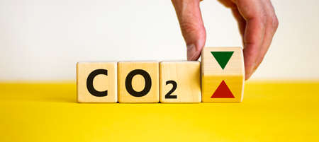 CO2 changes symbol. Concept words 'CO2' on cubes and blocks on a beautiful white background. Male hand changes the direction of an arrow symbolizing that CO2 are going down or vice versa. Business and CO2 concept. Copy space. Archivio Fotografico