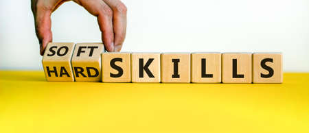 Hard skills versus soft skills. Hand flips cubes and changes the expression 'hard skills' to 'soft skills' or vice versa. Beautiful yellow table, white background. Business concept. Copy space.
