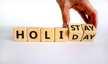 Holiday at home symbol. Male hand turnes cubes and changes the word 'holiday' to 'holistay'. Beautiful white background. Copy space, business and holiday at home concept.